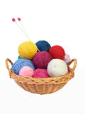 Colorful knitting yarn and needles in a basket. Colorful yarn balls and needles in a straw basket isolated on white background Stock Photography
