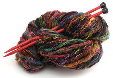 Colorful knitting yarn and two red needles. Colorful hank of knitting yarn Stock Image