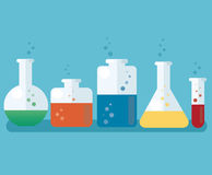Colorful laboratory filled with a clear liquid and blue background Stock Photos