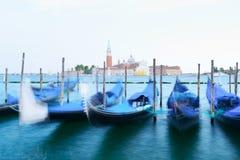 Row of gondolas parked on city pier Stock Photos