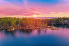 Colorful landscape at sunrise. Colorful nature sunrise landscape with pines trees, calm lake and beautiful colorful vivid sky Royalty Free Stock Photography