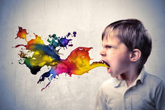 Colorful language. Angry child shouting with colored liquid coming out from his mouth Royalty Free Stock Photography