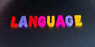 Colorful language. Text ' language ' composed of upper case colorful letters referring to speech and statements said to be in colorful language isolated on dark Stock Photography