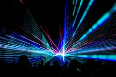 Colorful laser show nightlife club stage with party people crowd. Luxury entertainment with audience silhouettes in nightclub event, festival or New Year`s Eve royalty free stock photos