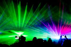 Colorful laser show nightlife club stage with smartphone selfies. Luxury entertainment with audience silhouettes in nightclub event, festival or New Year`s Eve stock photo