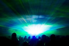 Colorful laser show nightlife hypnosis light tunnel people crowd. Luxury entertainment with audience silhouettes in nightclub event, festival or New Year`s Eve royalty free stock images