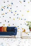 Colorful lastrico stickers pattern on a white wall and floor of a modern living room with a navy peony sofa. Real photo. royalty free stock images