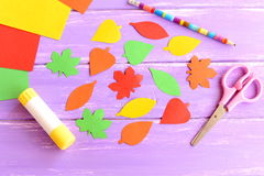 Colorful leaves cut from colored paper, scissors, glue stick, pencil, paper sheets on purple wooden background. Top view Royalty Free Stock Photos