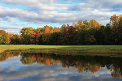 Colorful leaves of Fall reflecting on lake. Colorful autumn leaves reflecting on a lake on a farm in Indiana Stock Photography