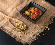 Lentil soup with chorrizo pieces. Colorful lentil soup in a blck ceramic bowl, a wooden spoon with lentil seeds on a rustic table cloth Stock Photos