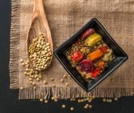 Lentil soup with chorrizo pieces. Colorful lentil soup in a blck ceramic bowl, a wooden spoon with lentil seeds on a rustic table cloth Royalty Free Stock Photo
