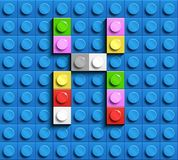 Colorful letter X from building lego bricks on blue lego background. Lego letter M. 3D design Stock Photo
