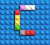 Colorful letter C from building lego bricks on blue lego background. Lego letter M. 3D design Stock Image