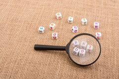 Colorful letter cubes behind a magnifying glass. Colorful alphabet letter cubes behind a magnifying glass Stock Photo