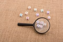 Colorful letter cubes behind a magnifying glass. Colorful alphabet letter cubes behind a magnifying glass Stock Photography