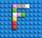 Colorful letter F from building lego bricks on blue lego background. Lego letter M. 3D design Royalty Free Stock Photos