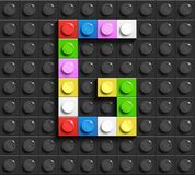 Colorful letter G from building lego bricks on black lego background. Lego letter M. 3D design Royalty Free Stock Photo