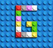 Colorful letter G from building lego bricks on blue lego background. Lego letter M. 3D design Royalty Free Stock Photo