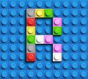 Colorful letter R from building lego bricks on blue lego background. Lego letter M. 3D design Stock Images