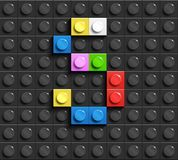 Colorful letter S from building lego bricks on black lego background. Lego letter M. 3D design Stock Image