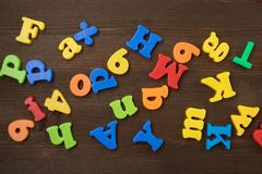 Colorful letters on background closeup. Colorful letters on brown, wooden background, closeup. Ordered in disarray royalty free stock images