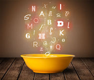 Colorful letters coming out of home cook soup bowl. On wood deck Royalty Free Stock Photo