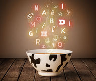 Colorful letters coming out of home cook soup bowl Stock Photos