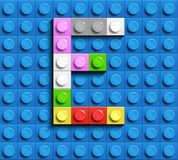 Colorful letters E of alphabet from building lego bricks on blue lego brick background. blue lego background. 3d letters C. Realis. Tic letters. 3D design Stock Images