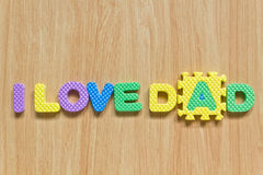 Colorful letters with I love dad. Isolated on wood texture Stock Image