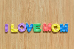 Colorful letters with I love mom. Isolated on wood texture Royalty Free Stock Photos