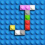 Colorful letters J of alphabet from building lego bricks on blue lego brick background. blue lego background. 3d letters C. Realis. Tic letters. 3D design Stock Photos