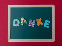 Colorful letters shaping the word Danke, thank you in german, on green board with wooden frame, red wall background. Danke, thank you, Colorful letters shaping royalty free stock photos
