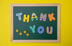 Colorful letters shaping the word thank you on green board with wooden frame, yellow wall background stock image