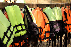 Colorful life jackets hanging on the row Royalty Free Stock Images