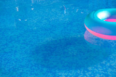 Colorful life preserver floating in a crystal clear pool. Colorful life preserver floating in a pool Royalty Free Stock Image