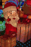 Colorful light decoration of Santa Claus raising his thumb up looking happy with piles of gift boxes Stock Photos