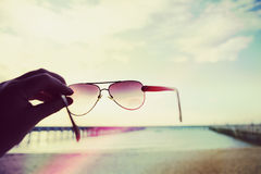 Colorful light leaks on hand holding sunglasses at a beach Stock Images