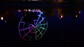 Colorful light reflections on water, abstract slow motion background of Ferris wheel`s ripple reflection