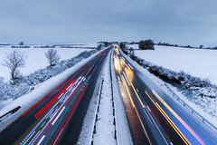 Cars Light Trails on Rural Motorway at Winter. Colorful light trails of multiple vehicles on scenic motorway in snowy winter royalty free stock photography