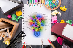 Colorful lightbulb sketch. Top view of messy desktop with colorful supplies, glasses and abstract lightbulb sketch in spiral notepad. Creative idea concept Royalty Free Stock Photos