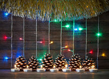 Colorful lights of garlands, fir cones and candles on the background of old barn boards. Festive new year and Christmas concept. Colorful lights of garlands, fir Stock Image