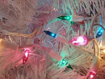 Colorful lights. Pretty colorful lights on a small white Christmas tree Stock Photography