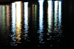Colorful lights reflecting on sea surface Royalty Free Stock Photo