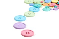 Colorful line of clothing buttons. Isolated colorful line of clothing buttons on white background Royalty Free Stock Photos