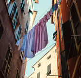 Colorful linen dry on rope between houses on old italian street Royalty Free Stock Image