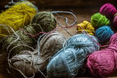 Colorful linen yarn for knitting with little color threads for knitting on old wooden surface. Close up royalty free stock images