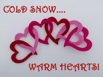 Colorful linked Valentine hearts on a bed of freshly fallen winter snow with Cold Snow Warm Hearts greeting.  Stock Photos