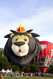Colorful lion and red air balloons taking off Stock Image