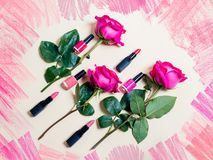 Colorful lipsticks, nail polishes and roses. On beige background Royalty Free Stock Images