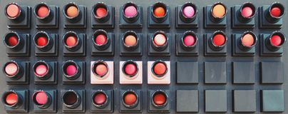 Colorful lipsticks tester on shelves for background stock photography